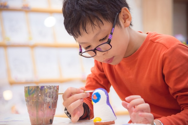 Junges asiatisches jungenmalereihandwerk durch farbe im klassenzimmer