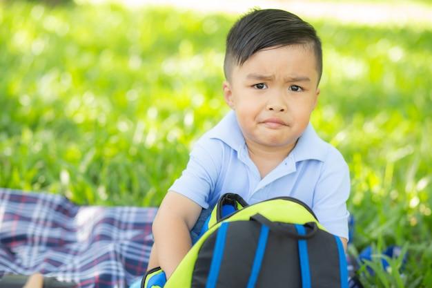 Junges asiatisches kind, das rucksack im rasen lächelt und öffnet