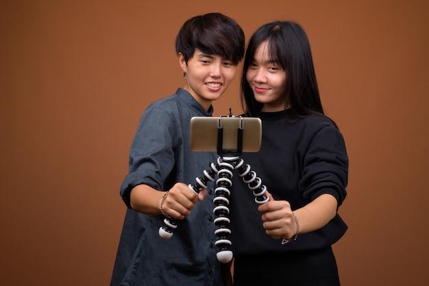 Junges asiatisches lesbenpaar zusammen und verliebt gegen braun