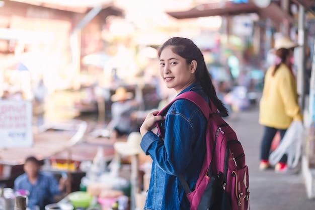 Junges asiatisches mädchen, das am schwebenden markt dumonoe saduak, in thailand geht