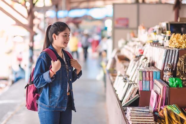 Junges asiatisches mädchen, das an sich hin- und herbewegendem markt dumonoe saduak geht