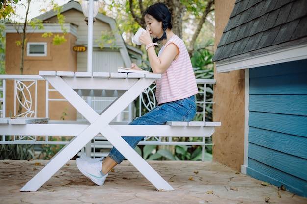 Junges asiatisches mädchen, das auf dem weißen holztisch sitzt, eine tasse kaffee trinkt und ein buch an den terrassen für entspannung liest