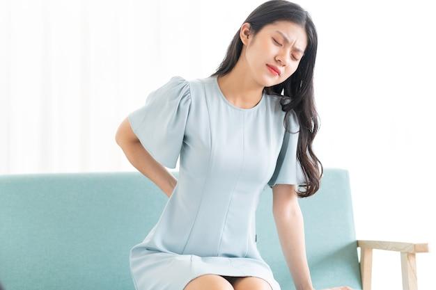 Junges asiatisches mädchen, das auf stuhl sitzt und sich müde fühlt