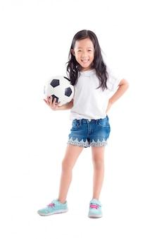 Junges asiatisches mädchen, das ball und lächeln über weißem hintergrund hält