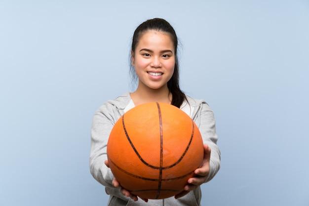 Junges asiatisches mädchen, das basketball über lokalisierter wand spielt