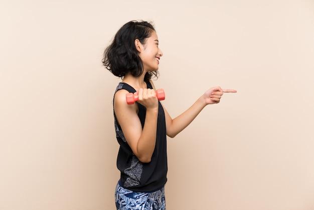 Junges asiatisches mädchen, das das gewichtheben über dem lokalisierten hintergrund zeigt auf die seite bildet, um ein produkt darzustellen