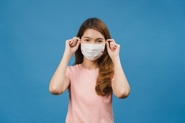 Junges asiatisches mädchen, das eine medizinische gesichtsmaske trägt, in freizeitkleidung gekleidet ist und die vorderseite isoliert auf blauer wand betrachtet