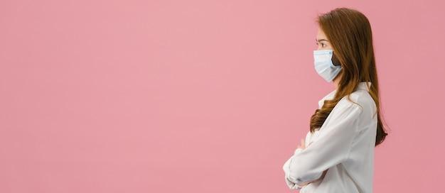 Junges asiatisches mädchen, das eine medizinische gesichtsmaske trägt, in legerem tuch gekleidet ist und den leeren raum einzeln auf rosafarbenem hintergrund betrachtet.