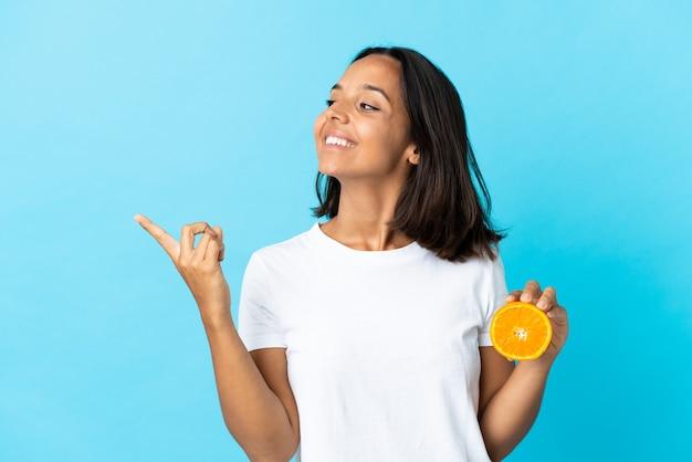 Junges asiatisches mädchen, das eine orange auf blau hält und beabsichtigt, die lösung zu realisieren, während ein finger angehoben wird