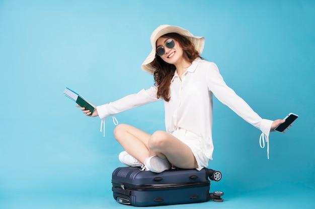 Junges asiatisches mädchen, das flugticket und telefon hält auf koffer hält