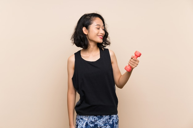 Junges asiatisches mädchen, das gewichtheben über getrenntem hintergrund mit glücklichem ausdruck bildet