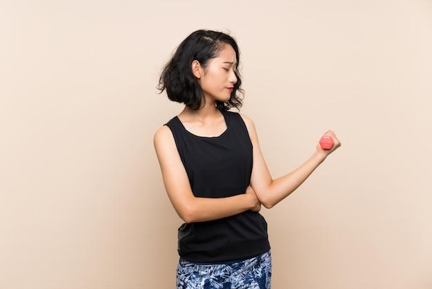 Junges asiatisches mädchen, das gewichtheben über lokalisierter wand mit traurigem ausdruck macht