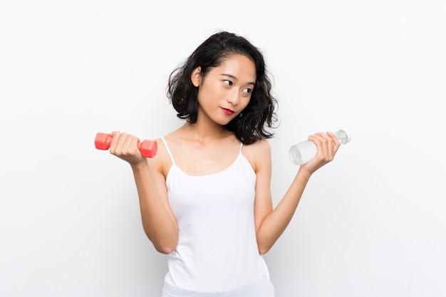 Junges asiatisches mädchen, das gewichtheben und mit einer flasche wasser macht