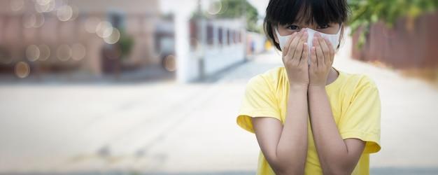 Junges asiatisches mädchen, das maske trägt, um covid 19 zu schützen, thailändisches kind tragen staubmaske. schützen sie pm 2.5 und stoppen sie das corona-virus-konzept