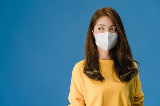 Junges asiatisches mädchen, das medizinische gesichtsmaske mit gekleidet in lässigem stoff trägt und leerraum lokalisiert auf blauem hintergrund betrachtet. selbstisolation, soziale distanzierung, quarantäne zur vorbeugung von koronaviren