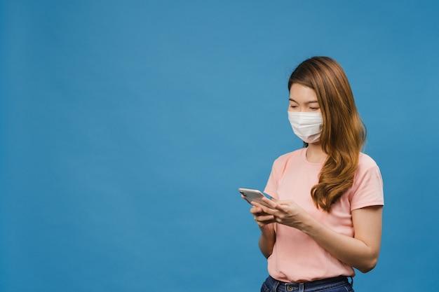 Junges asiatisches mädchen, das medizinische gesichtsmaske mit handy trägt und in freizeitkleidung gekleidet ist, die auf blauer wand isoliert ist?