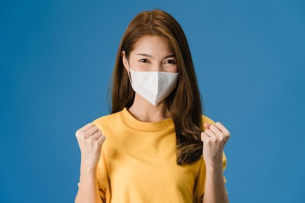 Junges asiatisches mädchen, das medizinische gesichtsmaske trägt, die friedenszeichen zeigt, ermutigt mit gekleidet in lässigem stoff und blick auf kamera lokalisiert auf blauem hintergrund. soziale distanzierung, quarantäne für koronavirus.