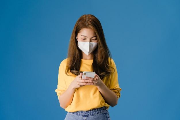 Junges asiatisches mädchen, das medizinische gesichtsmaske unter verwendung des mobiltelefons mit gekleidet in der freizeitkleidung lokalisiert auf blauem hintergrund trägt. selbstisolation, soziale distanzierung, quarantäne zur vorbeugung von koronaviren.