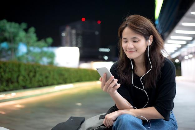 Junges asiatisches mädchen, das musik- oder videoinhalte über mobiltelefon hört