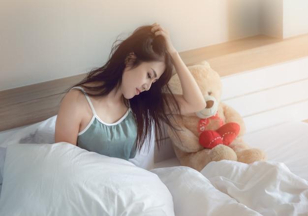 Junges asiatisches mädchen, das seinen kopf wegen des druckes über schlaflosigkeit auf dem weißen bett im schlafzimmer halten sitzt