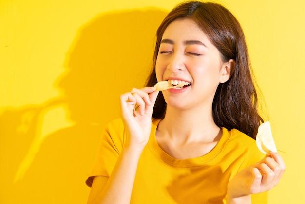 Junges asiatisches mädchen, das snack auf gelb isst