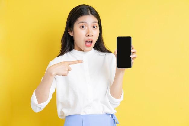 Junges asiatisches mädchen, das telefon mit ausdruck auf gelbem hintergrund hält