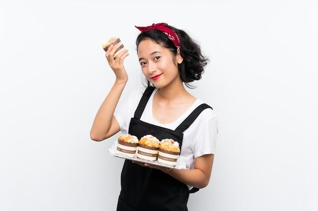 Junges asiatisches mädchen, das viele muffinkuchen über lokalisierter weißer wand hält