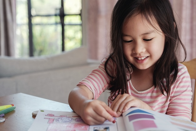 Junges asiatisches mädchen, das zu hause, homeschool ausbildung zeichnet