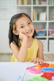 Junges asiatisches mädchen, das zu hause, mit der hand zur backe, bleistift hinter ohr und plastikzahlen auf schreibtisch sitzt
