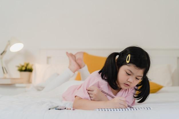 Junges asiatisches mädchen, das zu hause zeichnet. asiatisches japanisches frauenkinderkind entspannen sich karikatur des restspaßes des glücklichen abgehobenen betrages im skizzenbuch vor dem schlaf, der auf bett liegt, fühlen sich komfort und ruhe im schlafzimmer am nachtkonzept.