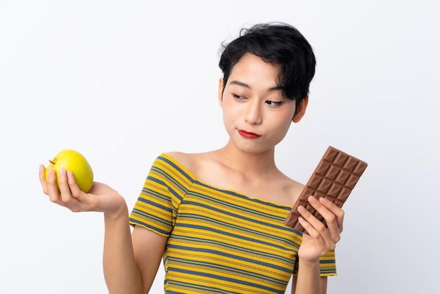 Junges asiatisches mädchen, das zweifel hat, während es eine schokoladentafel in einer hand und einen apfel in der anderen nimmt