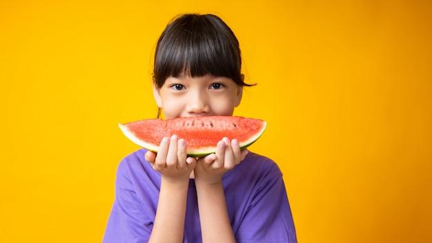 Junges asiatisches mädchen im violetten hemd, das wassermelone als großes lächeln, niedlich hält