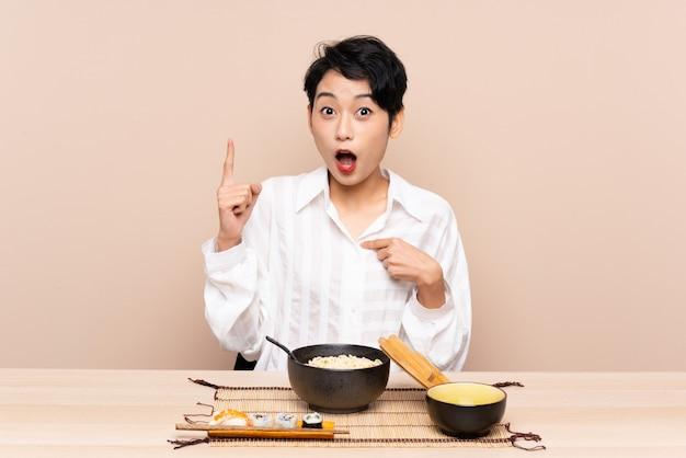 Junges asiatisches mädchen in einer tabelle mit schüssel nudeln und sushi mit überraschendem gesichtsausdruck