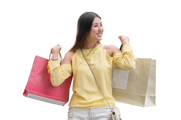 Junges asiatisches mädchen ist glücklich mit dem halten der einkaufstasche. isoliert auf weißem hintergrund