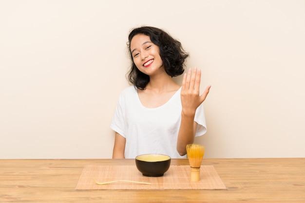 Junges asiatisches mädchen mit dem tee matcha, das einlädt, mit der hand zu kommen. schön, dass sie gekommen sind