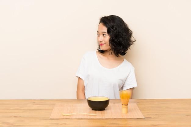Junges asiatisches mädchen mit dem tee matcha, das seite schaut