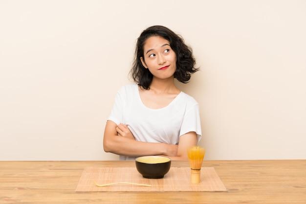 Junges asiatisches mädchen mit dem tee matcha, das zweifel macht, gestikulieren beim anheben der schultern