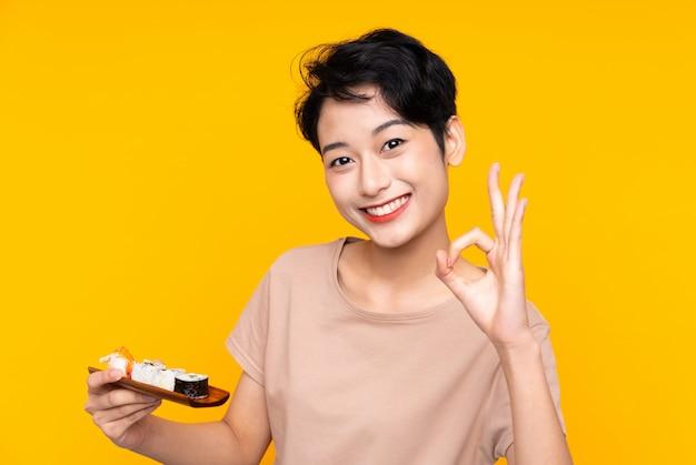 Junges asiatisches mädchen mit den sushi, die okayzeichen mit den fingern zeigen