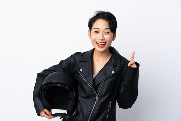 Junges asiatisches mädchen mit einem motorradhelm über isolierter weißer wand, die eine große idee aufzeigt