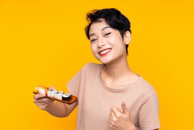 Junges asiatisches mädchen mit sushi mit daumen hoch, weil etwas gutes passiert ist