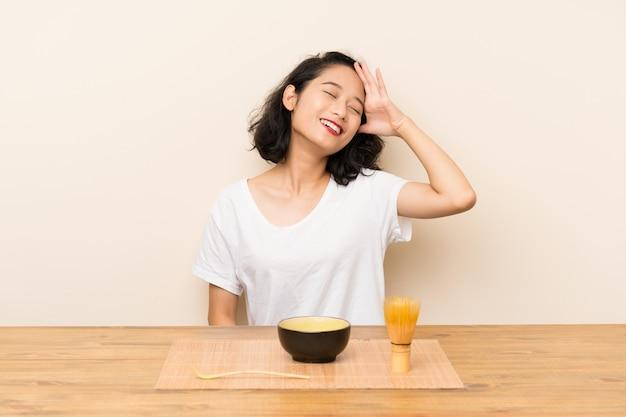 Junges asiatisches mädchen mit tee matcha hat etwas verwirklicht und die lösung beabsichtigt