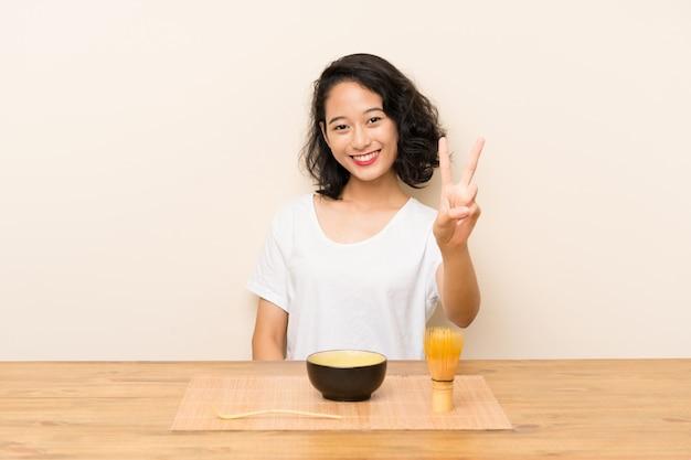 Junges asiatisches mädchen mit tee matcha lächelnd und siegeszeichen zeigend