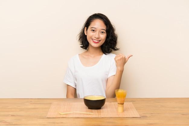 Junges asiatisches mädchen mit tee matcha mit den daumen oben, weil etwas gutes geschehen ist
