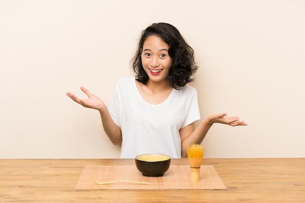 Junges asiatisches mädchen mit tee matcha mit entsetztem gesichtsausdruck