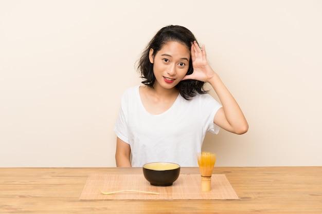 Junges asiatisches mädchen mit tee matcha mit überraschung und entsetztem gesichtsausdruck