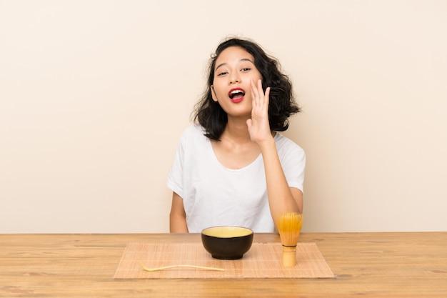 Junges asiatisches mädchen mit tee matcha schreiend mit dem breiten mund öffnen sich