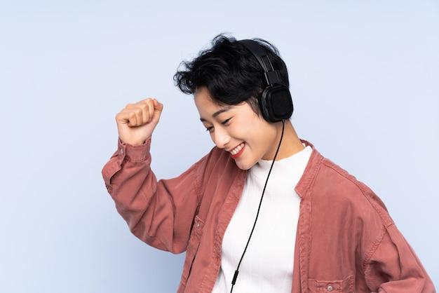 Junges asiatisches mädchen über hörender musik und tanzen der lokalisierten blauen wand