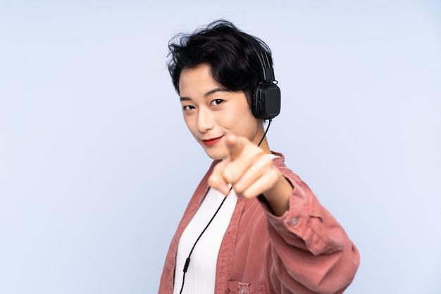Junges asiatisches mädchen über isolierter blauer wand, die musik hört und nach vorne zeigt