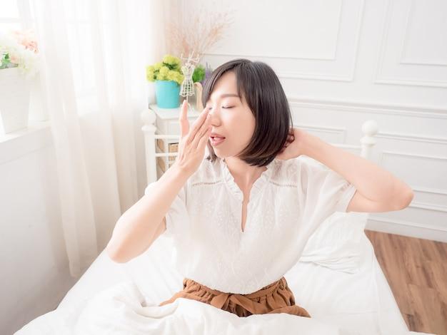 Junges asiatisches mädchen wacht morgens auf und streckt die arme auf dem bett aus