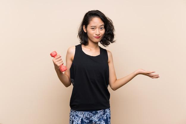 Junges asiatisches mädchen, welches das gewichtheben über der lokalisierten wand macht zweifel gestikulieren beim anheben der schultern macht